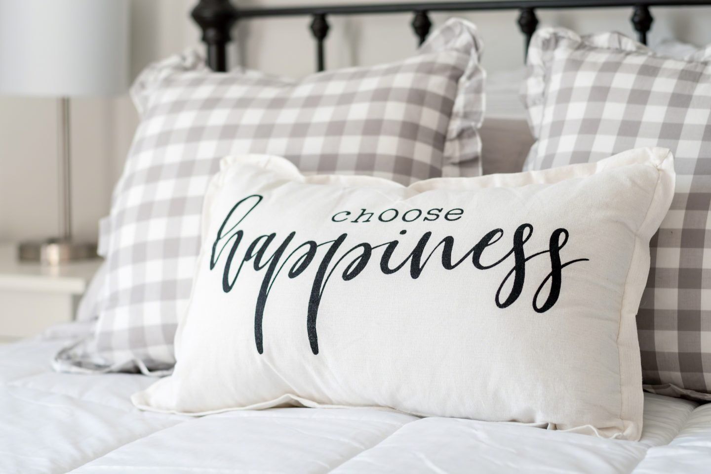 """Bedroom decor - """"choose happiness"""" pillow on iron bed"""