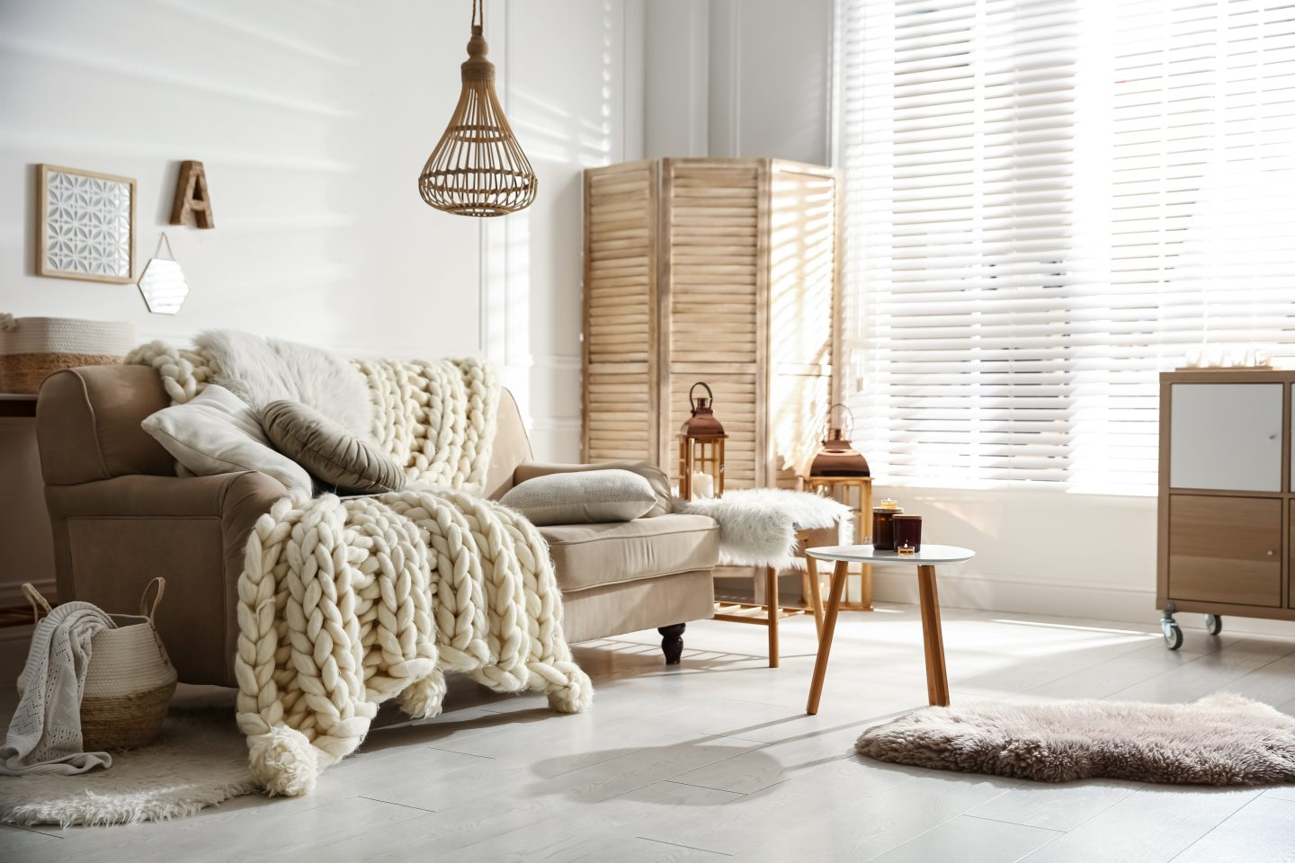 Cozy living room interior with beige sofa, knitted blanket and cushions